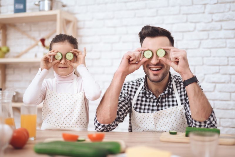 father and daughter playing with cucumbers