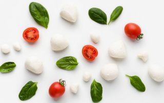 Colorful caprese ingredients pattern made of cherry tomatoes, basil and cheese on white background. Caprese salad recipe concept,