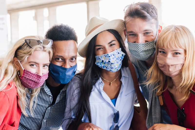 Portrait group of young happy friends wearing face mask during Covid pandemic smiling at the camera. Multiracial people taking a selfie outdoor having fun together. New normal lifestyle concept.