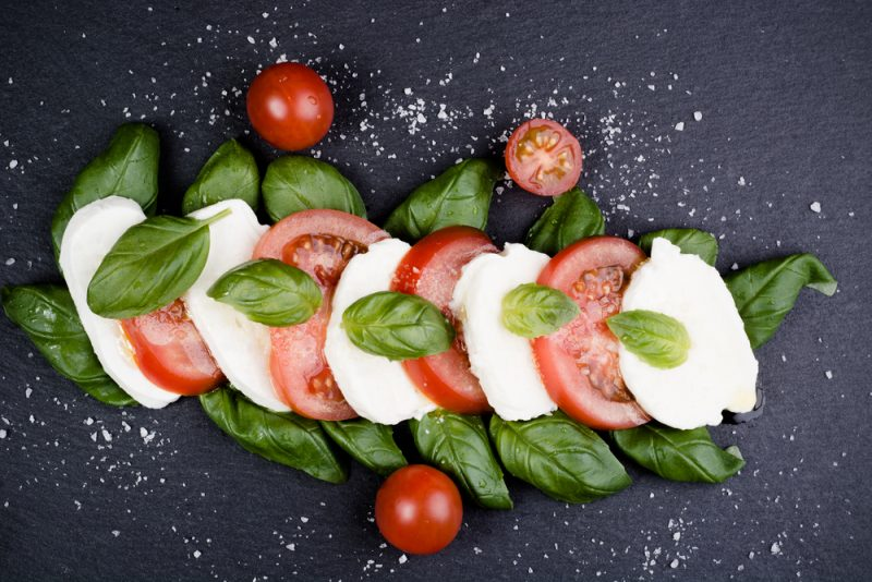 A traditional Italian Caprese with mozzarella, basil and tomatoes is displayed.