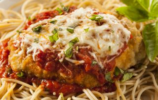 A closeup of a chicken parmesan dish, made with chicken, cheese and spaghetti noodles.