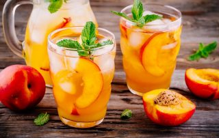 Two glasses of peach sangria, a pitcher, and several peaches can be seen on a wooden surface.