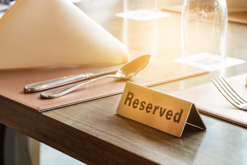A close up of a brown dining table at a restaurant. You can see a reserved sign in the center of the table. and a light brown placemat with a folded napkin, a spoon and fork to the left of the sign.