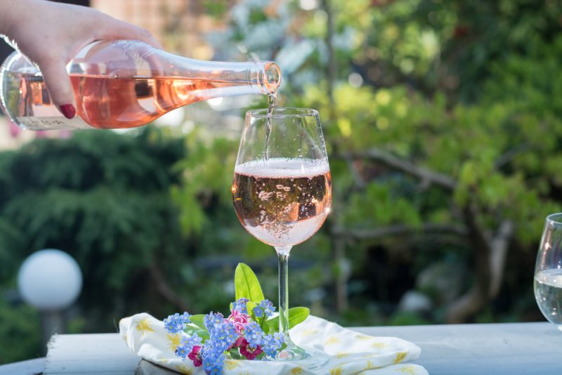A woman's hand is shown pouring a bottle of Rosé into a wine glass on a white tabletop. A napkin and a small blue flower are seen in front of the glass.