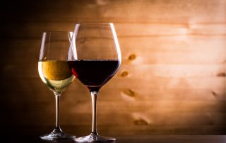 Two glasses of wine sit on a black surface with a wood background. The left glass contains white wine, and the right one contains red wine.