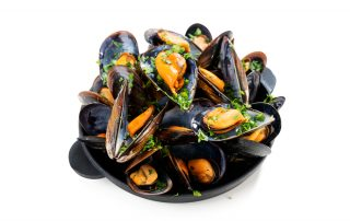 A close up image of a black bowl filled with mussels.