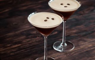A close up of the espresso martini beverage in two martini glasses. Three coffee beans can be seen floating in each glass.