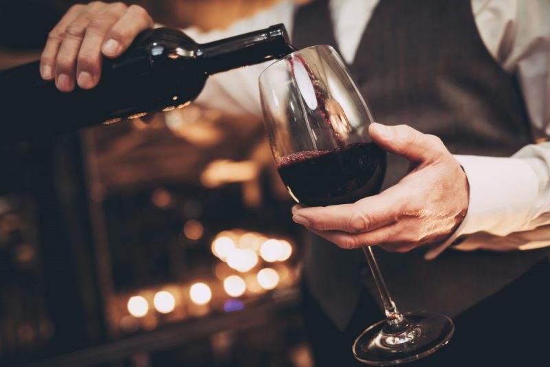 A waiter in uniform pours a bottle of red wine into a wine glass,