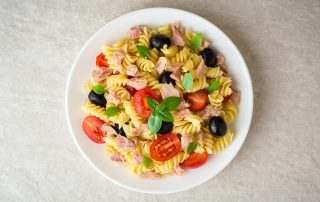 A top down view of a white bowl on a darker white surface filled with pasta salad. You can see tomatoes, tuna, pasta, black olives and collard greens in the dish.